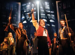 Ashley Gilmour as Enjolras and Company - Photo: Johan Persson